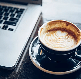 Coffee cup and computer to illustrate how outsourcing your SEO can help you relax knowing your website will soon rank well on Google.