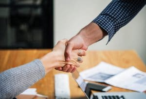 Two people shaking hands over a computer workstation | SEO for a Private Practice Website | Simplified SEO Consulting