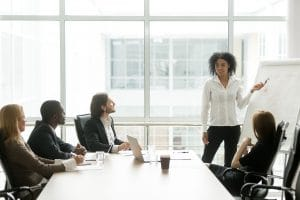 A woman stands in front of a large white notepad giving a presentation in a conference room full of business people | SEO Training for Therapists | Simplified SEO Consulting