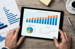 A photo of a man holding a tablet with a increasing bar graph on the screen | Therapists SEO services are available with monthly SEO packages available for private practice clinicians | Simplified SEO Consulting