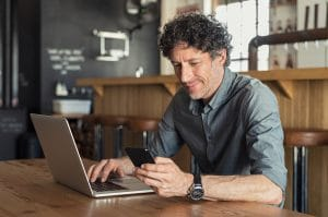 Photo of man in grey shirt typing on a laptop smiling | SEO Monthly Packages & SEO training workshop | Simplified SEO Consulting