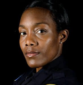 Photo of police officer, looking at the camera. Officer is a woman in uniform.