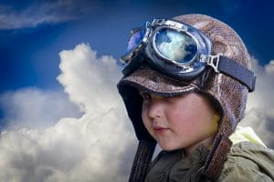 Child pilot, looking directly at private practice owners on this SEO website over background clouds