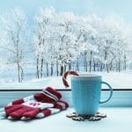 A snowy scene with a cup of cocoa and mittens to represent the slow holiday season many therapists and small business owners see. Focusing on learning search engine optimization can be a great way to use the slow time this winter!