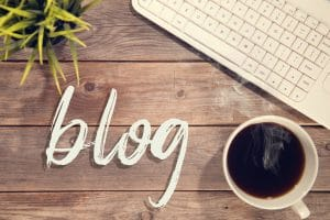 The word blog written in white on a table next to a cup of coffee and a keyboard. Blogging can help therapists and psychologists in search engine optimization for their private practice websites.