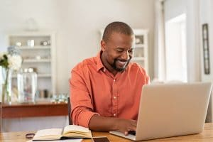 smiling male therapist writing a blog post for his counseling clinic | SEO for therapists | Simplified SEO Consulting
