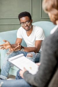 A young adult man and his therapist in a counseling session to show how digital marketing and a good website can help a Christian Counselor find clients.