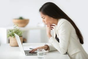 Concerned asian therapist looks at her laptop as she worries about SEO. Simplified SEO Consulting can help you improve site speed and more.
