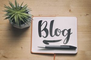 "The word ""blog"" on a paper with a pen and small cactus to represent how important blogging is for therapists and private practice owners working on their search engine optimization."