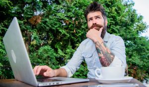 Bearded man with tattoo sleeves blogging and looking thoughtful about SEO when posting a blog. Simplified SEO can help therapists and therapy websites rank in search engines like Google and Bing!