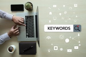 "Photo of a masculine hand touching a keyboard on a laptop and the word ""Keywords."" Represents how this article discusses how small business owners can optimize a website with a focus on keyword placement."
