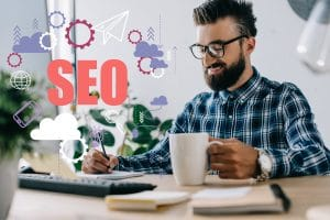 successful therapist and business owner with cup of coffee and computer writing notes at workplace with SEO icons