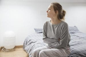 Photo of woman in her room looking stressed to show how Covid-19 social distancing can increase anxiety and depression and show how therapists can help.