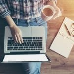woman at laptop drinking a cup of coffee working on her private practice's website. Begin SEO services with Simplified SEO consulting