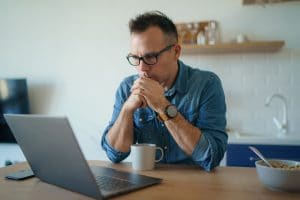middle age man sits at his computer wondering what SEO keywords to use to reach his ideal clients on Google. He gets help from a member of the Simplified SEO Consulting team.