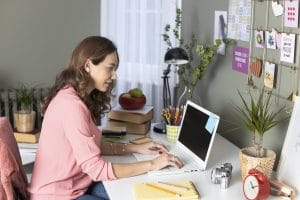 female therapist works in her at home office writing blogs after researching seo keywords that her ideal clients are looking for. She learns tips from members of the Simplified SEO consulting staff