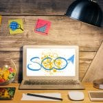 Creative designer desktop with table lamp SEO sketch on laptop scree various devices and stickers with rocket icons on wooden wall. SEO and internet concept