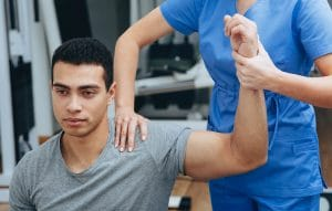 Athlete with a shoulder injury working with a PT or OT. Photo represents how SEO can help occupational therapists and physical therapists reach more patients.