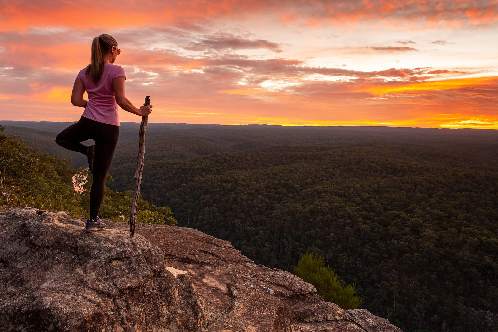 Woman standing on one foot holding a stick, on the top of a cliff overlooking the sunset. With comprehensive SEO services for therapists and counselors, you can focus on what you do best as a private practice owner. Get SEO help for therapists with Simplified SEO Consulting.