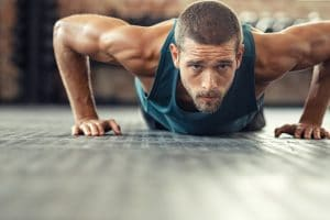 A man does push ups on a gym floor. As a personal trainer, he recently started working with Simplified SEO Consulting to get his website ranking higher.
