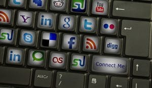 A keyboard with social media icons is displayed. This is an important concept to consider when evaluating the role of social media in boosting SEO.