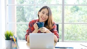 Happy woman working from home on her laptop drinking coffee. She works with an SEO specialist from Simplified SEO Consulting to rank better on Google
