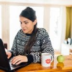 Pretty woman in a sweater works on SEO for online therapy website after getting SEO services with Simplified SEO consulting