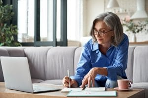 mature woman writes in her notebook planning content for her service page and working on her SEO for private practice. She gets help from an SEO expert at Simplified SEO consulting