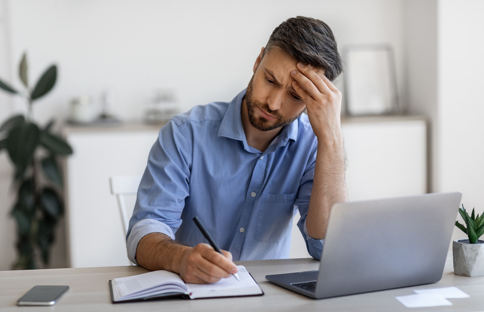 middle age man at his computer looks frustrated writing content for SEO. He gets tips on readability and writing content for his private practice from SEO specialist at Simplified SEO Consulting