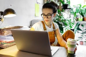 stylish woman in glasses holds a coffee and works on optimizing her private practice webpage. She gets SEO tips on readability from an SEO specialist at Simplified SEO Consulting
