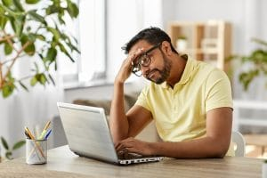 frustrated man on his computer with his head on his hand. He just found out that his Google my Business listing was removed because he has an online only private practice. He's worried about the rankings for his online therapy practice.