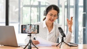 A woman is recording for her podcast. She is hoping to build podcast seo with Simplified SEO Consulting.