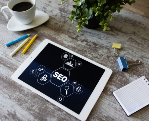 Table in wooden table near coffee and plant. SEO for mental health professionals is very important to get your people, but ethical seo is a must. Learn how optimizing SEO for backlinking can help you build credible traffic to your website.