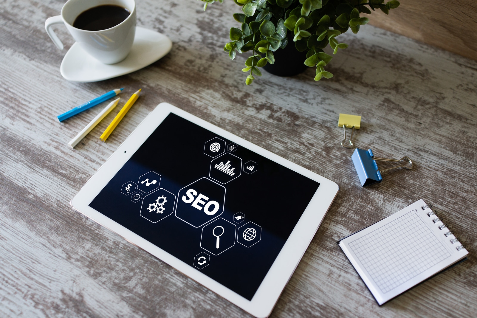 "iPad on a desk with a ""SEO"" graph on the screen. Coffee and assorted office supplies surround the iPad. You can get custom SEO training for therapists and private practice websites with an SEO expert. Your SEO training will help you learn SEO."