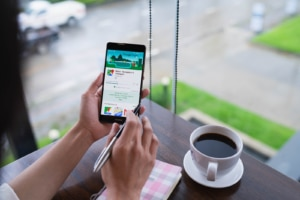 Google Maps on a cell phone next to a cup of coffee at a cafe. Representing the importance of letting Google know where you're located when working on your SEO. Learn SEO from a seo specialist at Simplified SEO consulting
