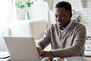Black man works on his laptop at home optimizing his website and works with an SEO specialist for SEO training at Simplified SEO consulting