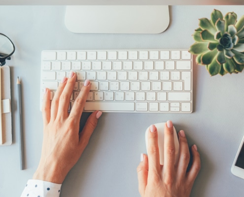 A person types on a laptop. They are blogging for seo.