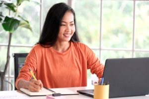 Asian woman works on her SEO and adds location indicators to her private practice website. She gets SEO help from an SEO consultant at Simplified SEO Consulting