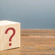 """Image of a wooden block with a red question mark on its side. This image illustrates the many questions clients have about SEO, including """"how long does SEO take?"""""""