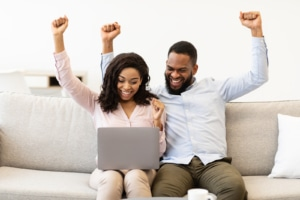 A couple raise their hands in celebration as they look at their laptop. This could represent social media and SEO success. Learn more about SEO marketing for therapists and how SEO training can help your practice!