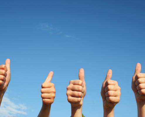 """Image of five hands holding a """"thumbs up"""" against a blue sky background. This image represents the good SEO for psychiatrists that happens when they work on getting backlinks."""