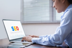 """Image of a person using a laptop at a desk with the screen reading """"SEO search engine optimization"""" in the search bar. Working on SEO for a private practice website can help therapists get ranking."""