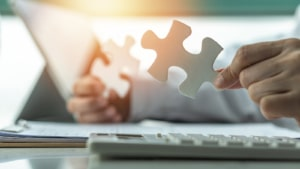 Image of a person holding two puzzle pieces up. Therapists working on their private practice website can benefit from working with our company providing services for SEO for private pracitices.