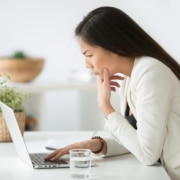 An Asian woman stands looking confused at her laptop. This could represent misunderstanding an off page SEO checklist. Learn more about on page and off page SEO, and how we can help with off page optimization.