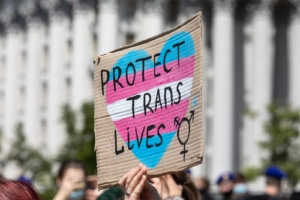 """Image of a person holding up a sign reading """"protect trans lives."""" This image illustrates how trans letter writing can help therapists provide inclusive services to trans people. An SEO services consultant can share more!"""