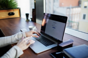 Person typing on laptop in office on desk. Learning what content to build out helps seo for therapists. Learn how to find keywords to rank on a trauma page and what SEO for trauma therapists is all about here!
