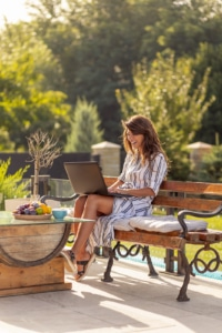 woman sits on a bench working on private practice SEO on her laptop. She learns how to get to the top of google from an SEO specialist at Simplified SEO who specializes in SEO for therapists.