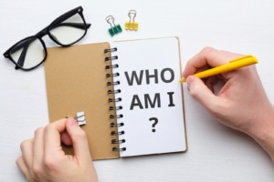 """Person writing in journal with """"who am I"""" on page. Helping others understand you as a therapist matters. Learn how to write website about me pages and the best meet the team pages from our SEO specialists today!"""