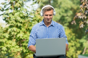 man in headphones works on his laptop at a park. He learns about optimizing his private practice website from an SEO specialist with Simplified SEO Consulting who specializes in SEO for therapists