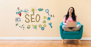 """A woman on a laptop looks off pensively with the cartoon graphic """"seo"""" on the wall. This represents the SEO training that Simplified SEO Consulting can provide. Contact us for support with therapist SEO today."""
